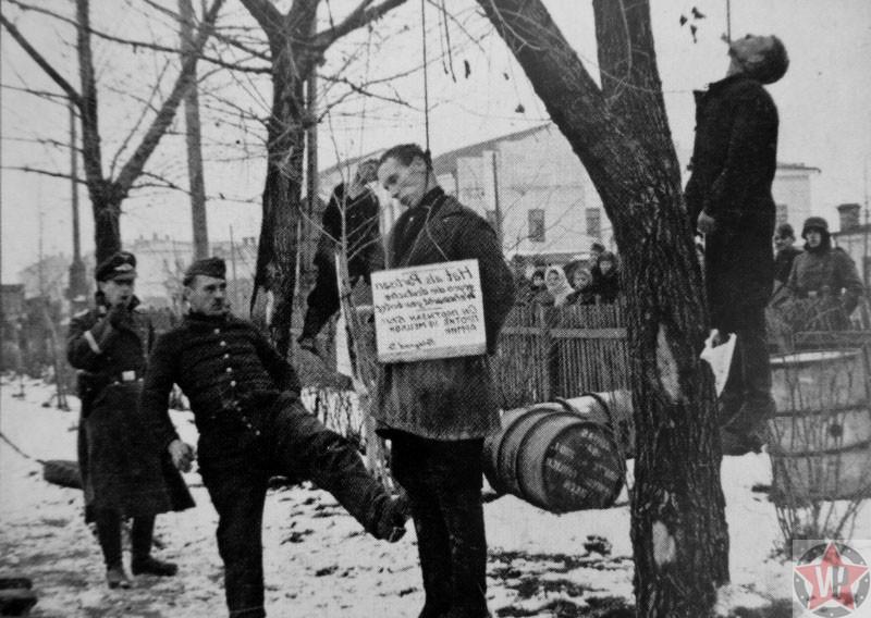 Солдат Вермахта пинает тело повешенного Советского партизана