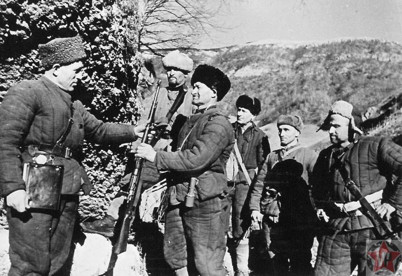 Командир отряда сопротивления вручает бойцу боевой карабин