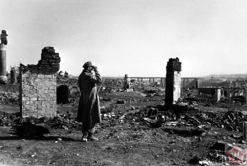 Немецкий офицер смотрит в бинокль недалеко от моста в Сталинграде