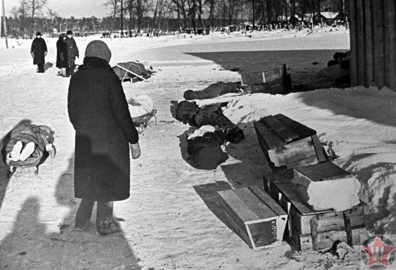 Женщина стоит у тел умерших жителей блокадного Ленинграда