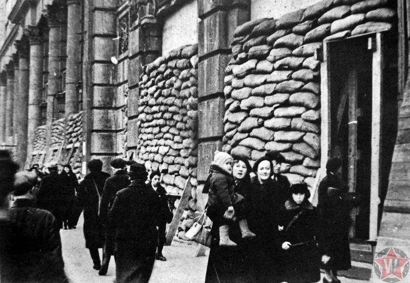 Жители на улице блокадного Ленинграда у зданий