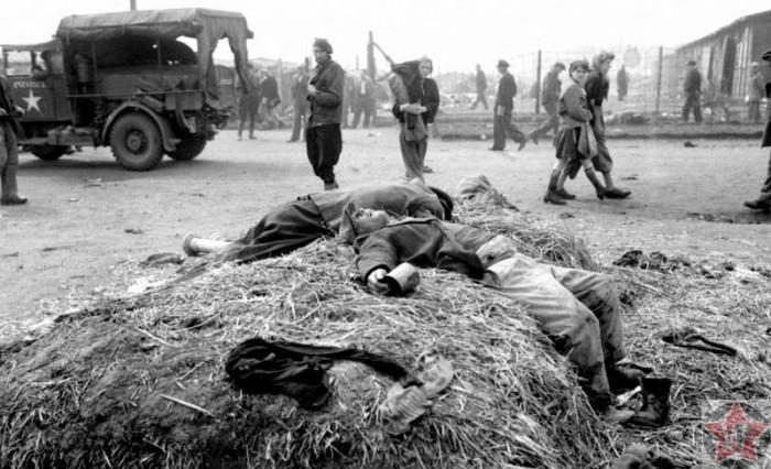 Умерший и умирающий узники концлагеря лежат на куче соломы.